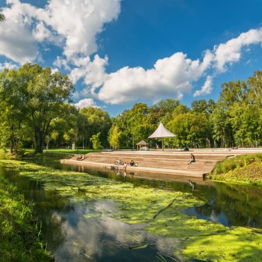 Zdjęcie przedstawia Park Centralny w Olsztynie poprzez który płynie rzeka Łyna.