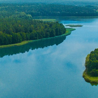 Zdjęcie przedstawia jezioro z lotu ptaka, wzdłuż którego linii brzegowej gęsto rosną drzewa. Na środku jeziora widnieją dwie wysepki.