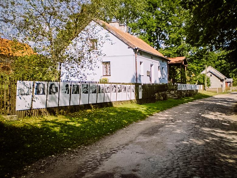 Zdjęcie przedstawia wiejską drogę przy której stoją prostokątne niskie domy, a na drewnianym płonie wiszą białe plakaty ze zdjęciami ludzi i opisami.