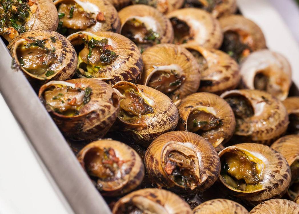 Zdjęcie ukazuje zbliżenie skorupek ślimaków wypełnionych farszem. Skorupki mają brązowy kolor, a ich wznętrze jest zapieczone na złocisto.