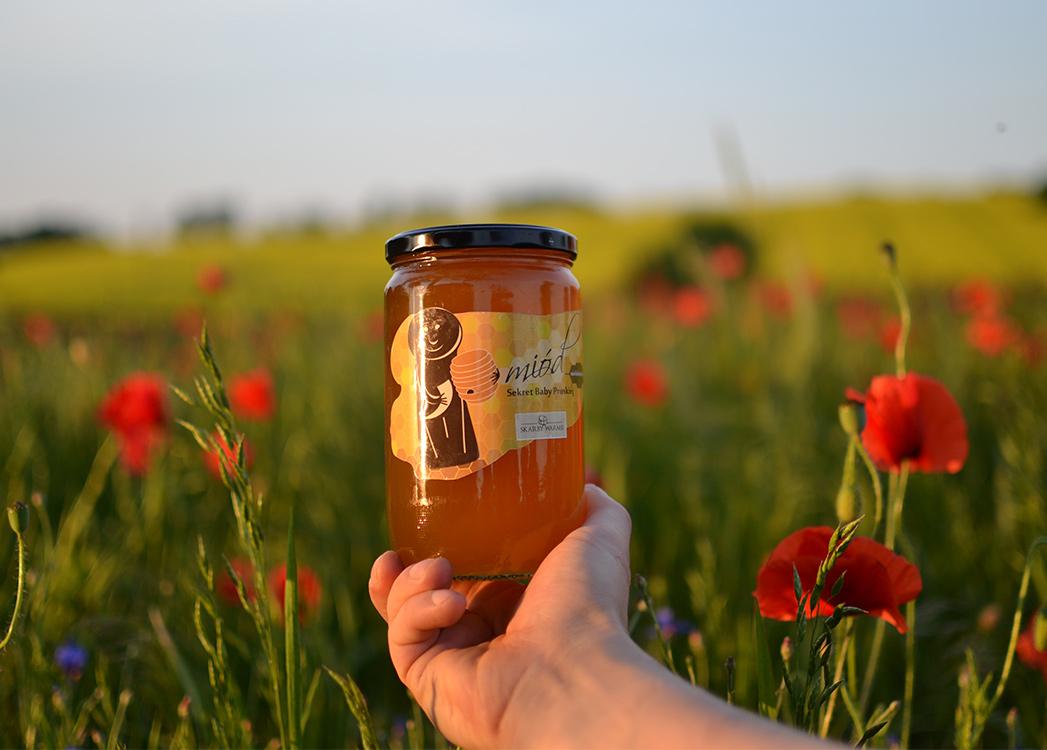 Trzymany w dłoni słoik miodu na tle mazurskiej łąki z kwiatami maku.
