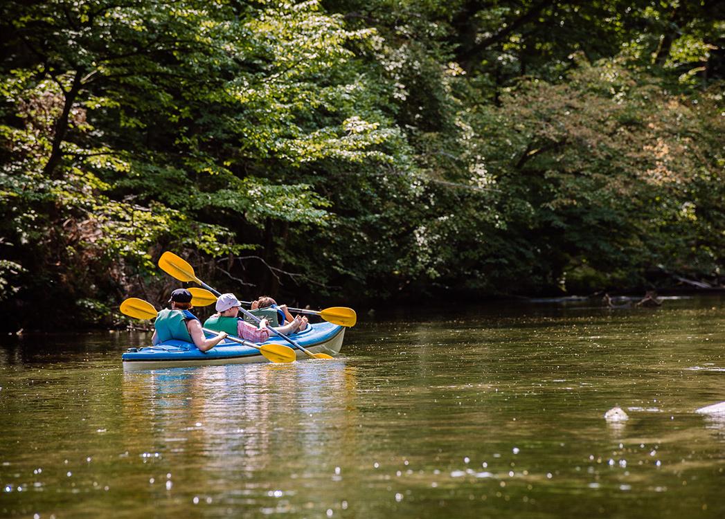 Zdjęcie przedstawia trójosobowy kajak płynący z załogą przez rzekę Krutynię.