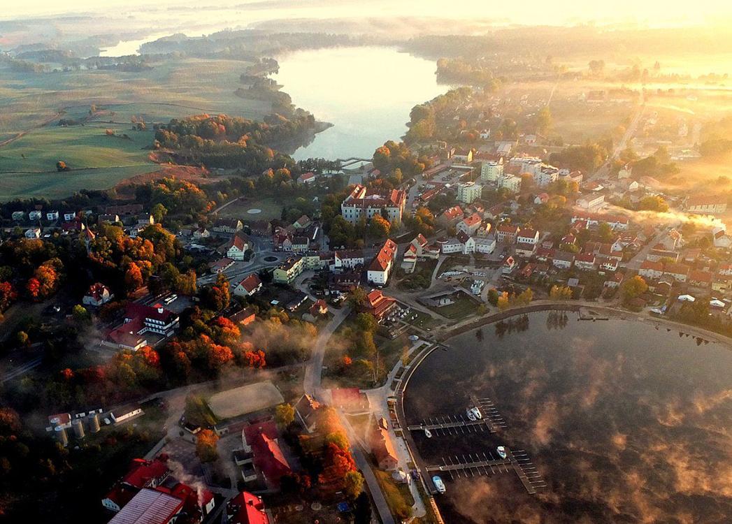 Zdjęcie zrobione z lotu ptaka miejscowości Ryn położonej między jeziorami. Nad jeziorami i domami unosi się poranna mgła ukazując jak miasto leniwie budzi się do życia.