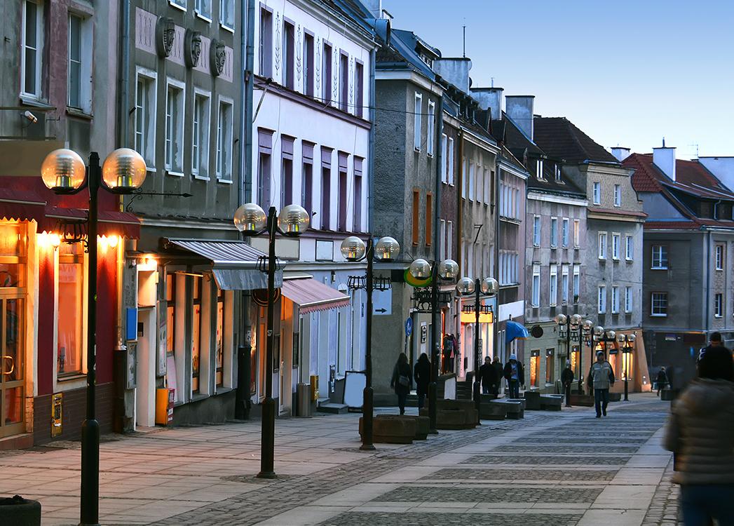 Promenada spacerowa Starego Miasta w Olsztynie podczas zmierzchu. Po prawej stronie promenady budynki mieszkalne z witrynami sklepów i lokali usługowych. Po środku promenady dreptak z kilkoma spacerującymi mieszkańcami miasta.