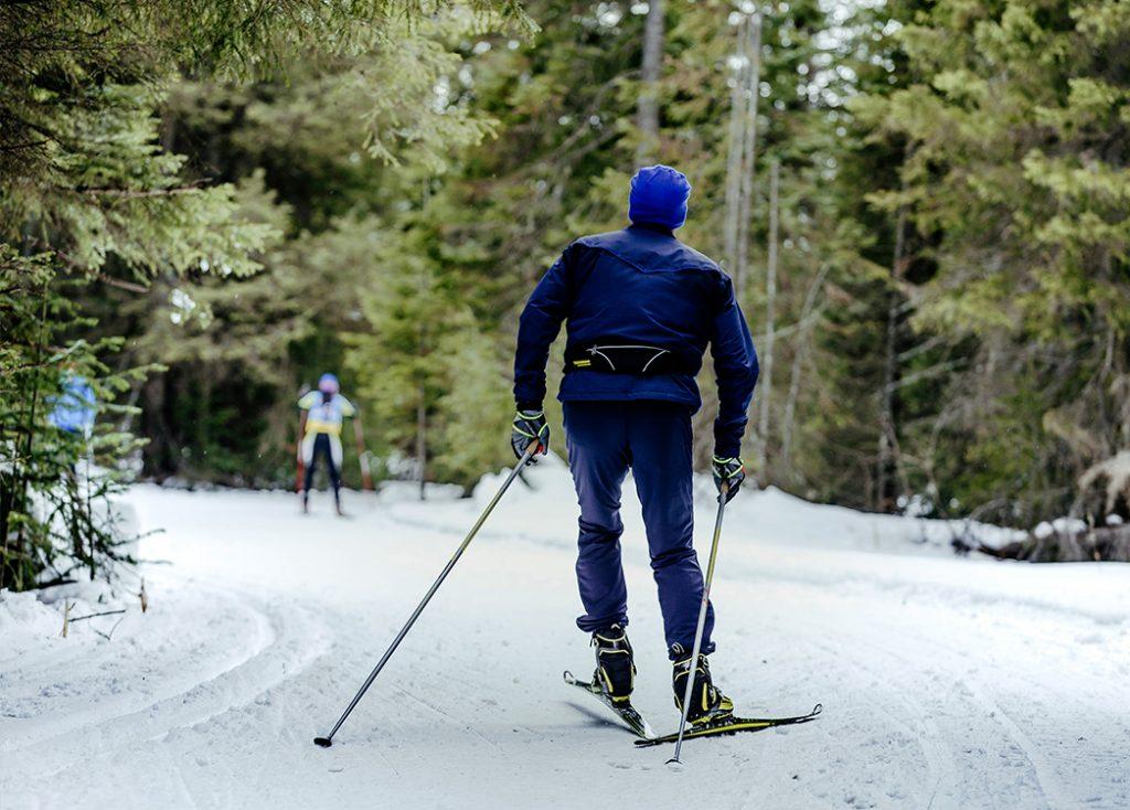 Zdjęcie przedstawia mężczyznę jedzącego na nartach biegówkach na ośnieżonej ścieżce w lesie.