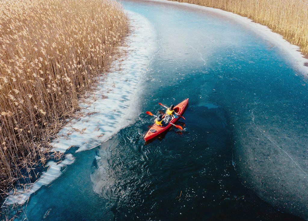 Zdjęcie przedstawia spływ kajakiem Krutynią podczas zimy. Czerwony dwuosobowy kajak płynie przez zamarzniętą wodę, a trawy dookoła mają słomiany kolor.