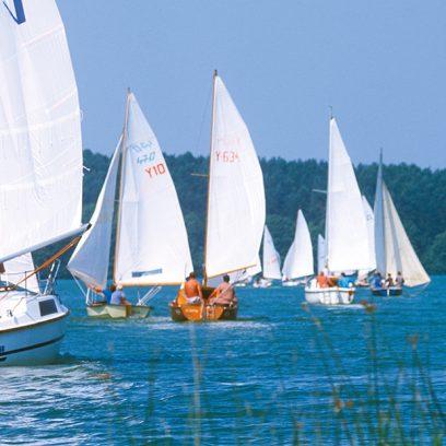 Zdjęcie przedstawia pływające na jeziorze białe łodzie z załogami letnią porą.