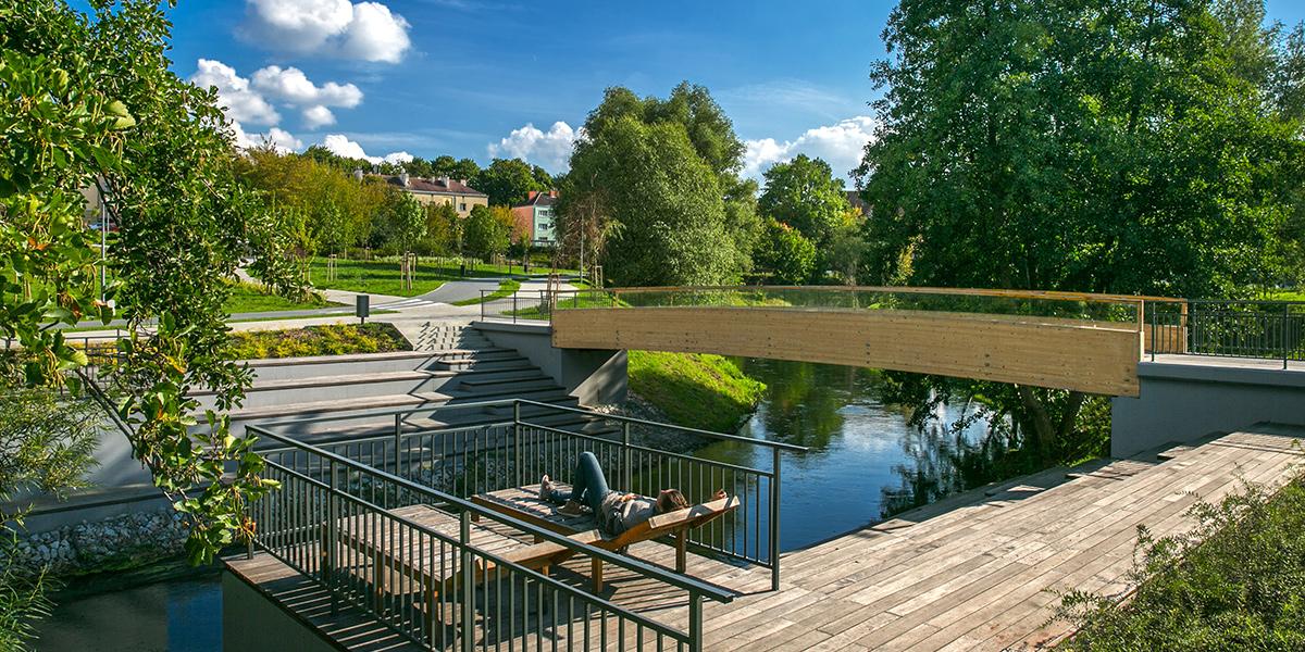 Zdjęcie przedstawia rzekę Łynę płynącą przez Parku Centralny w Olsztynie. Nad rzeką biegnie drewniana kładka, a na wyłożonym drewnem brzegu na drewnianym leżaku leży kobieta.
