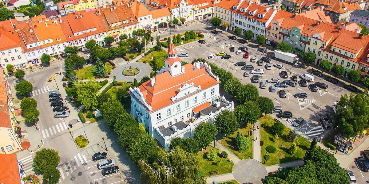 Zdjęcie z lotu ptaka przedstawia budynek z licznymi zdobieniami i wieżą wyłaniającą się z się z dachu, dookoła którego jest park, parkingi, a z każdej strony za ulicami kamienice w różnych kolorach.