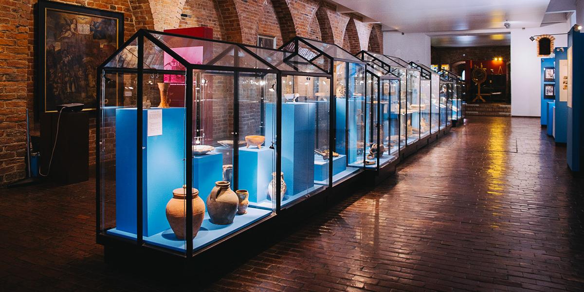Zdjęcie przedstawia wnętrze sali muzealnej będącej częścią Muzeum Mikołaja Kopernika we Fromborku, gdzie w gablotach można zobaczyć liczne gliniane naczynia.