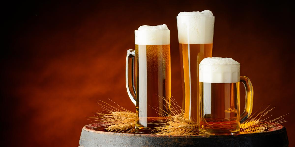 Zdjęcie przedstawia trzy różne rodzaje kufli wypełnionych piwem. Kufle stoją na beczce, na której również leżą złote kłosy zbóż.