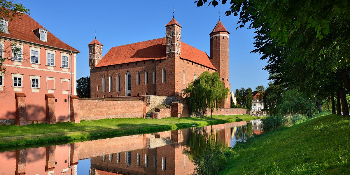 Zamek w Lidzbarku Warmińskim, zbudowany z czerwonej cegły otoczony fosą. Po lewej stronie zamku widoczna część budynku hotelu Krasicki. Między fosą a zamkiem znajduje się wypielęgnowany pas zieleni.