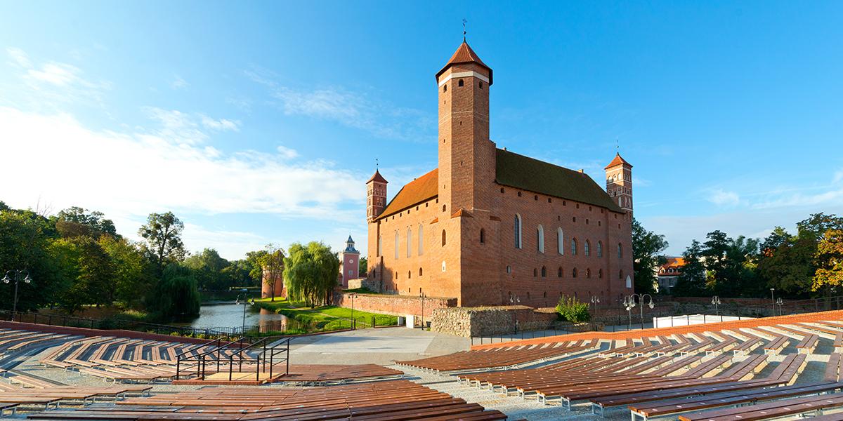 Zdjęcie przedstawia scenę z widownią na świeżym powietrzu w Lidzbarku, za którą stoi murowany wysoki zamek oraz płynie rzeka.