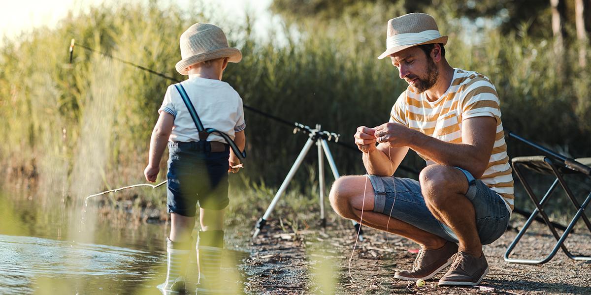 Tata z synem w trakcie letniego wędkowania nad brzegiem mazurskiego jeziora, zakładający haczyk na żyłkę wędki. Chłopczyk moczy kij w wodzie obok taty.