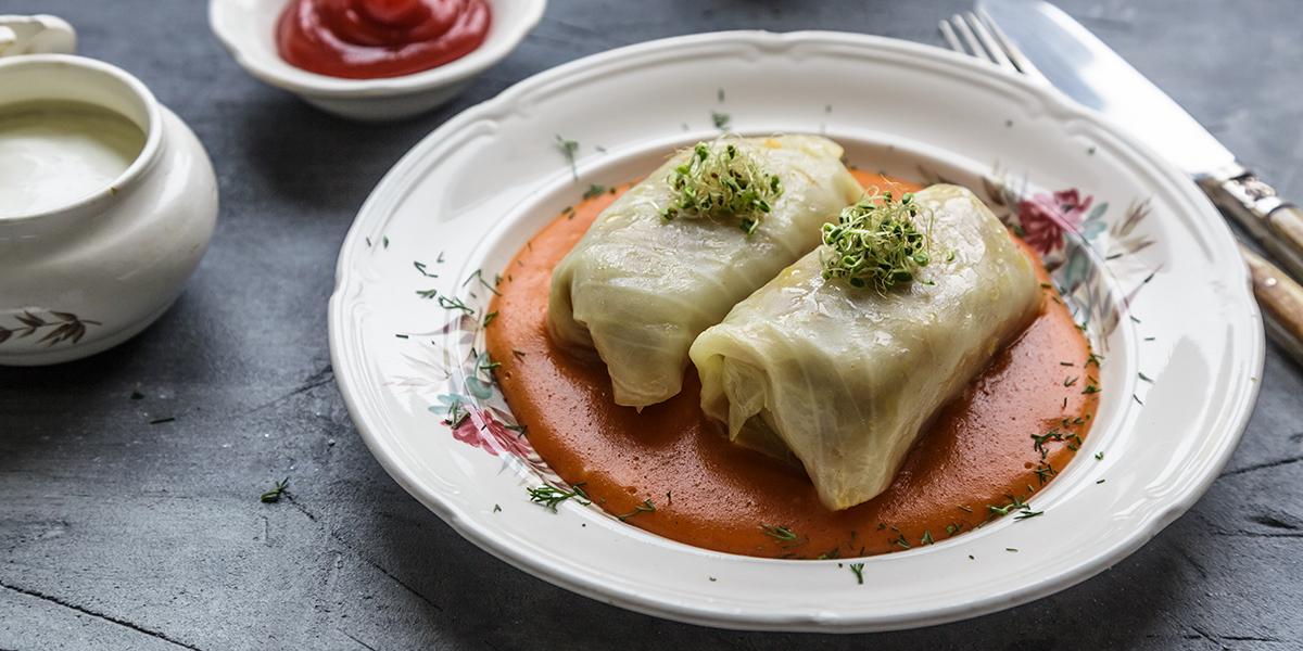 Na stole podane danie na talerzu a w nim dwa gołąbki w sosie własnym ozdobione rzeżuchą. Obok talerza znajdują się sztućce, keczup na małym talerzyku oraz sos do smaku.