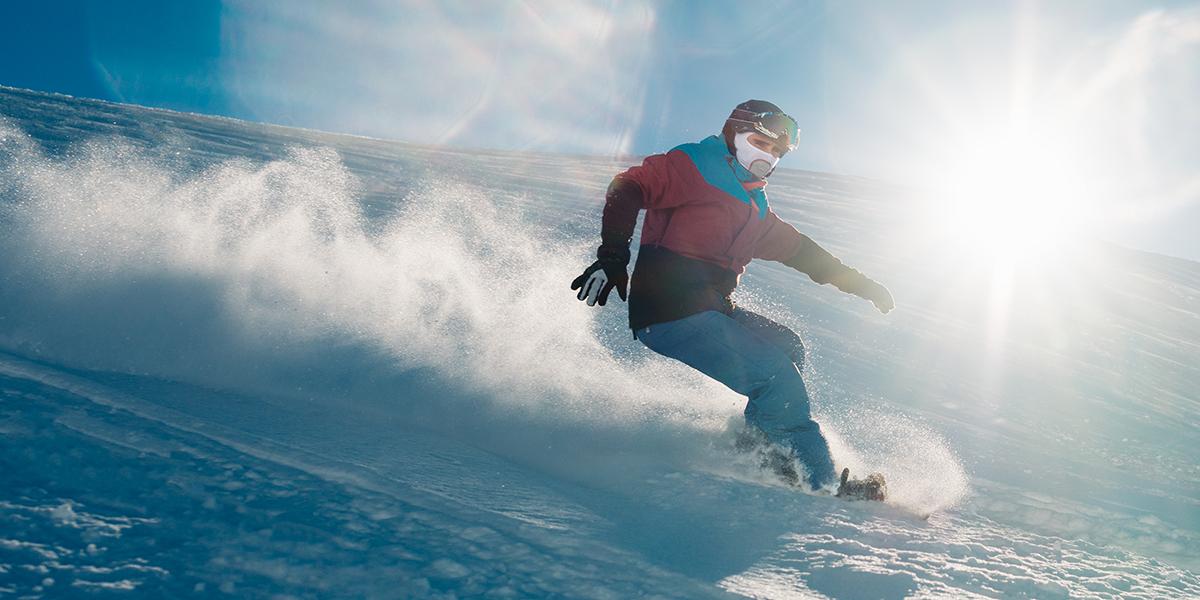 Zdjęcie przedstawia zbliżenie mężczyzny zjeżdżającego po ośnieżonej górze na snowboardzie.