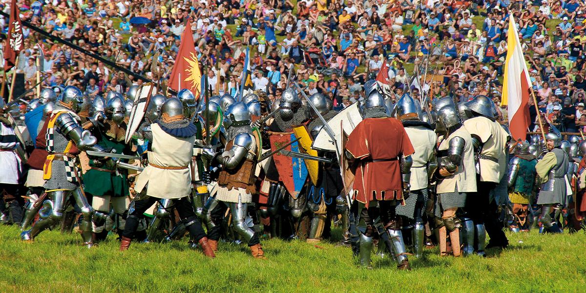 Inscenizacja Bitwy pod Grunwaldem. Na pierwszym palnie rycerze podczas walki, wszyscy w hełmach i pełnym rynsztunku bojowym. Na drugim planie bardzo duża liczba widzów siedzący na polanie i oglądających bitwę.