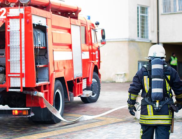 Wóz straży pożarnej podczas akcji zaparkowany przy bloku mieszkalnym, obsługiwany przez strażaka w pełnym strażackim ekwipunku.