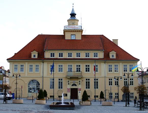 Od frontu budynek Ratusza Miejskiego w Olsztynku na tle fontanny i rynku miejskiego - promenady