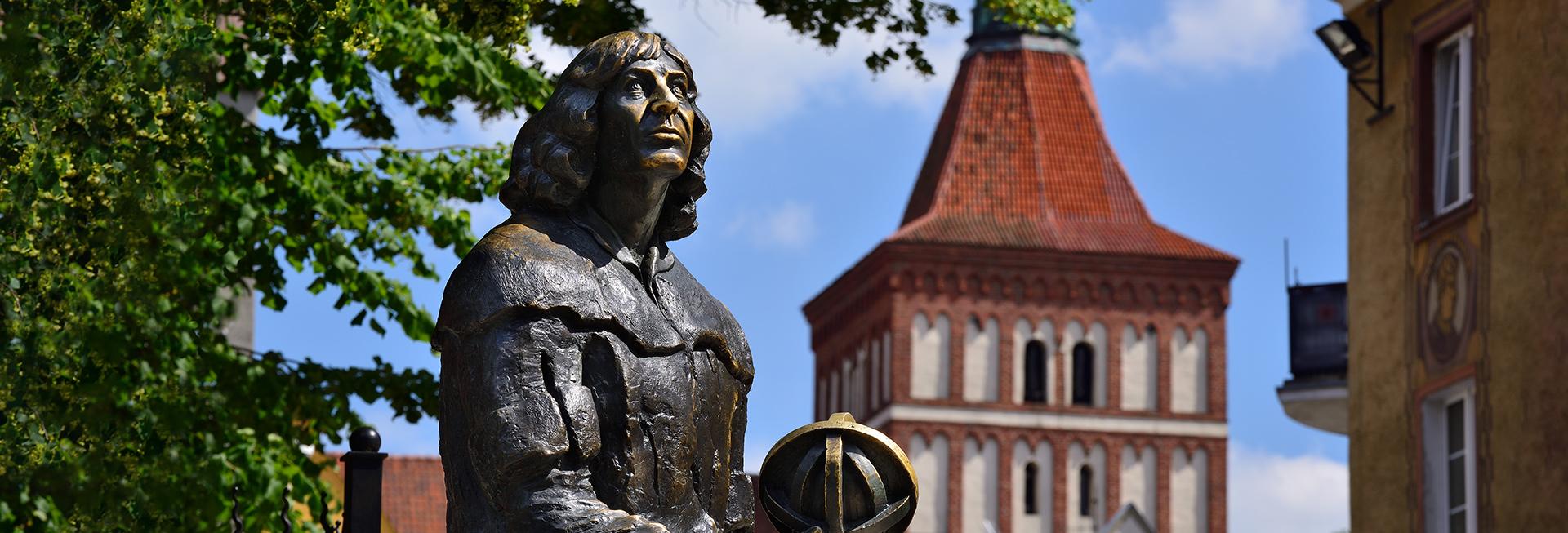 Zdjęcie przedstawia pomnik z brązu Mikołaja Kopernika, który stoi na olsztyńskim starym mieście.