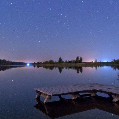 Zdjęcie przedstawia pomost nad spokojnym jeziorem nocą. Zza linii jeziora widać światła domów.