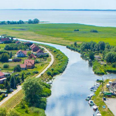 Zdjęcie z lotu ptaka ukazujące ujście rzeki Pasłęki do Zalewu Wiślanego. Po prawej i lewej stronie rzeki znajdują się zabudowania mieszkalne dalej łąki a na horyzoncie widzimy Zalew Wiślany.