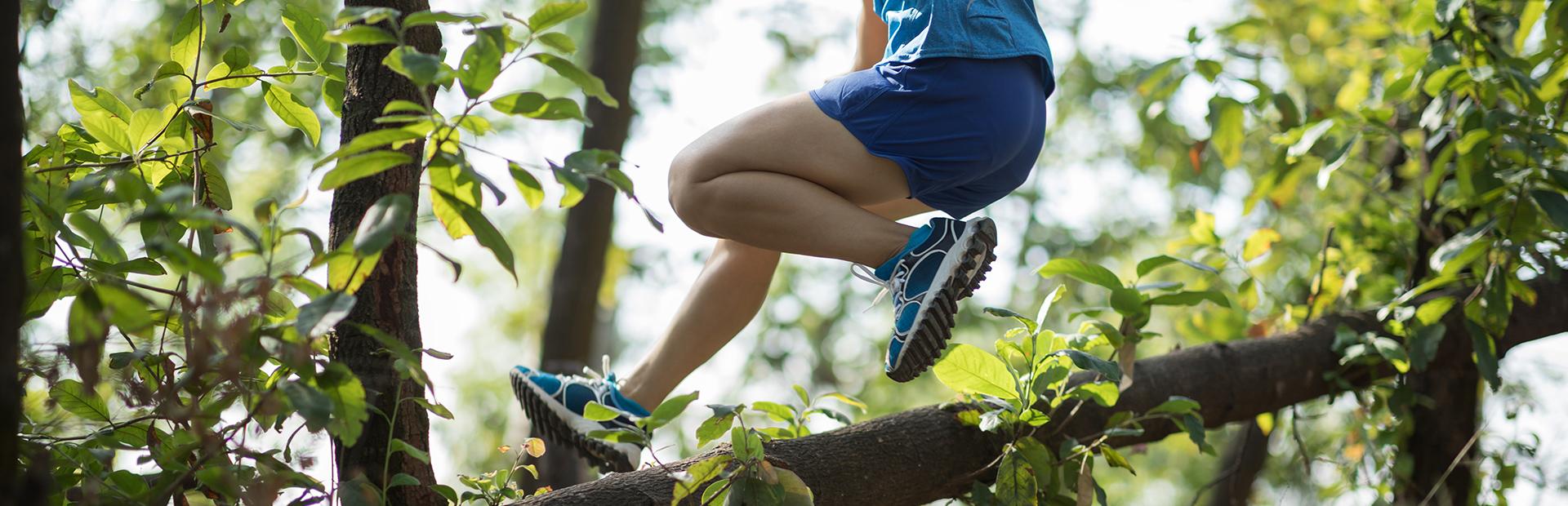 Biegacz podczas przeskakiwania przeszkody, zwalonego konaru drzewa na leśnej ścieżce.