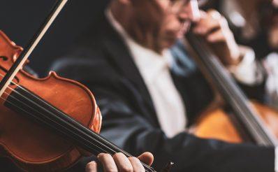 Dwóch muzyków podczas koncertu muzyki klasycznej w galowych garniturach, grających na skrzypcach i kontrabasie.