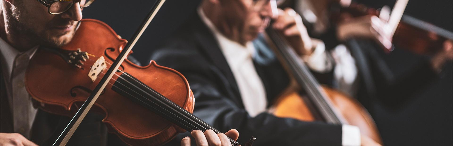 Zdjęcie ilustracja przedstawiające orkiestrę symfoniczną podczas koncertu.