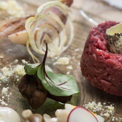 Zdjęcie ukazuje finezyjnie podanego tatara wołowego. Na uformowanym czerwonym mięsie ułożone jest przepiórcze jajko, a dookoła ułożona jest kompozycja z grzybów, warzyw i jajka ugotowanego na twardo.