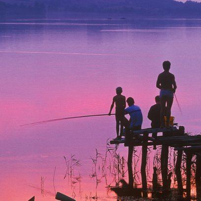 Zdjęcie przedstawia czworo ludzi w różnym wieku stojących na małym pomoście. Ludzie łowią ryby przy zachodzie słońca.