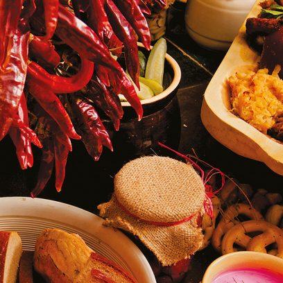 Zestaw dań podany na stole w drewnianej tacy na którym widzimy golonkę, kluski, kapustę, surówki oraz zieleninę. Obok dania dostawiona jest zupa żurek, chleb, ogórki, papryka i konfitury a dla ozdobienia zestawu dodany jest wiszący czosnek.