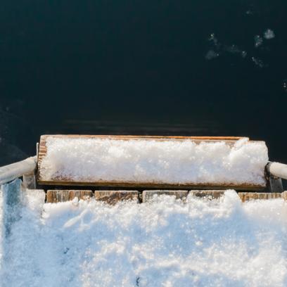Zdjęcie przedstawia zbliżenie zejścia z oblodzonego pomostu do jeziora na którym również jest lód. Drabinkę do zejścia trzymają ręce osoby, która zapewne za chwilę będzie morsować.