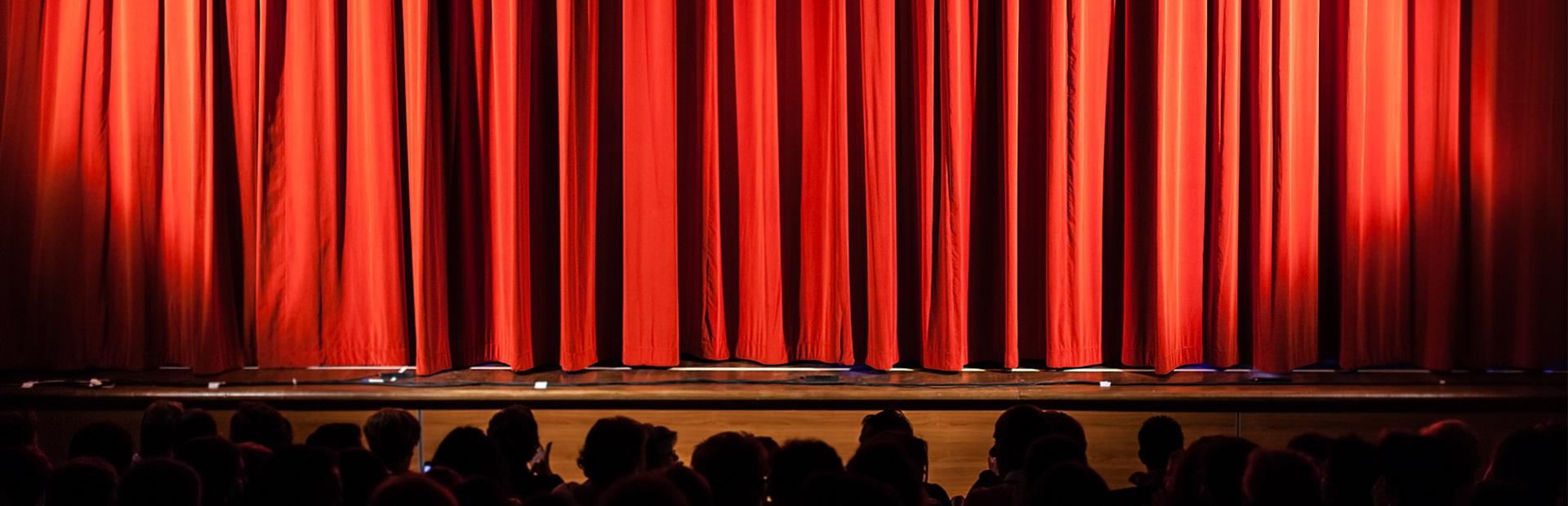Scena teatralna zasłonięta czerwoną kotarą.