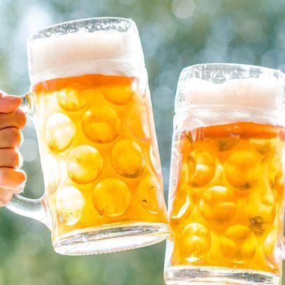 Zdjęcie ukazuje zbliżenie na dwa kufle wypełnione złocistym piwem, które trzymają prawdopodobnie mężczyźni w koszulach w kratę.