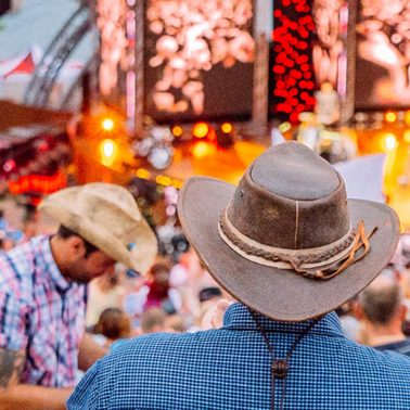 Zdjęcie przedstawia amfiteatr w Mrągowie podczas Pikniku Country na którym bawią się ludzie z kowbojskimi kapeluszami na głowach.