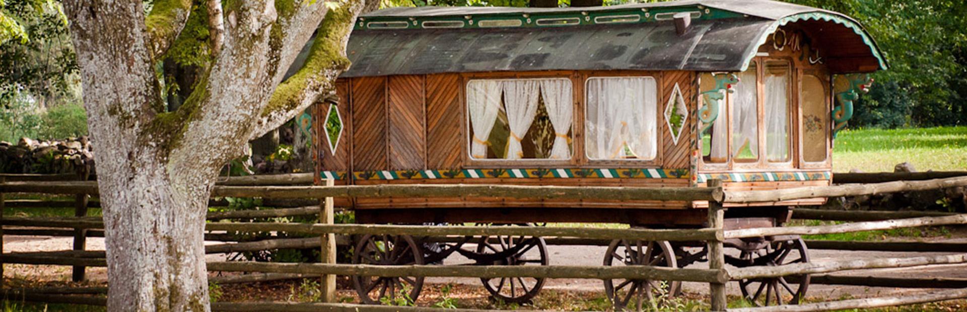 Zdjęcie przedstawia cygański drewniany wóz stojący przy drodze. W oknach widać białe firanki.
