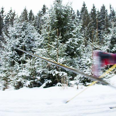 Zdjęcie przedstawia mężczyznę żwawo biegnącego na nartach przez ośnieżoną drogę.