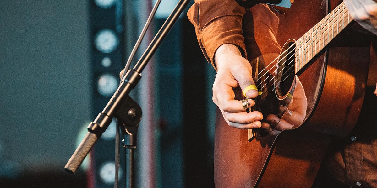 Gitara podczas koncertu na której wykonywany jest przez artystę utwór. Obok instrumentu statyw z mikrofonem.