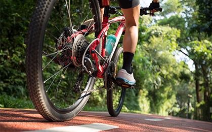 Zdjęcie ilustracja przedstawiająca jadącego rowerzystę.