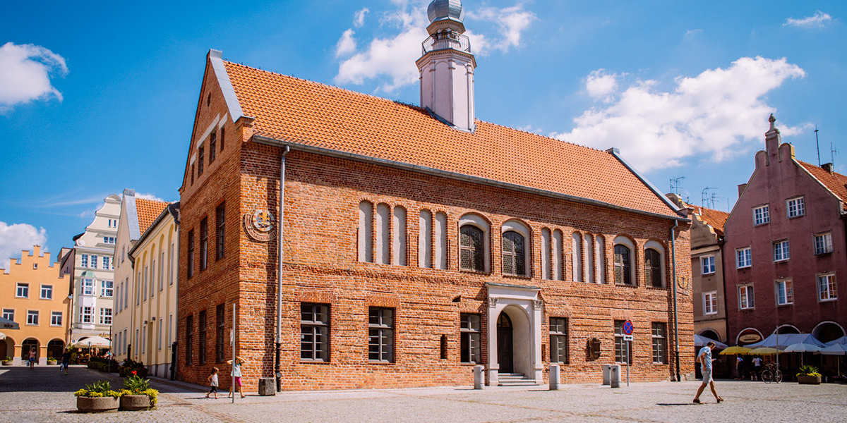 Zdjęcie przedstawia stary ratusz stojący w centrum starego miasta w Olsztynie. Budynek wykonany jest w czerwonej cegły, ma liczne okna a do jego środka prowadzą wysokie brązowe drzwi.