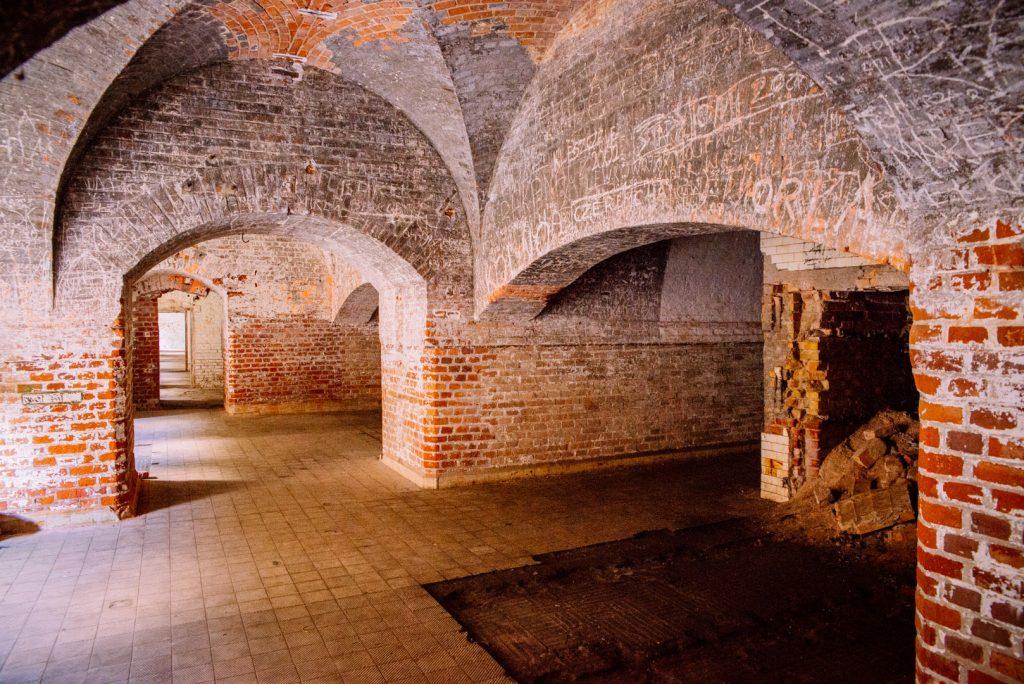 Wnętrza Twierdzy Boyen w Giżycku, charakterystyczne grube mury ścian i stropów zbudowane z czerwonej cegły. Na otynkowanych częściach stropów widnieją niechlujne ręczne napisy i rysunki pozostałe po turystach.