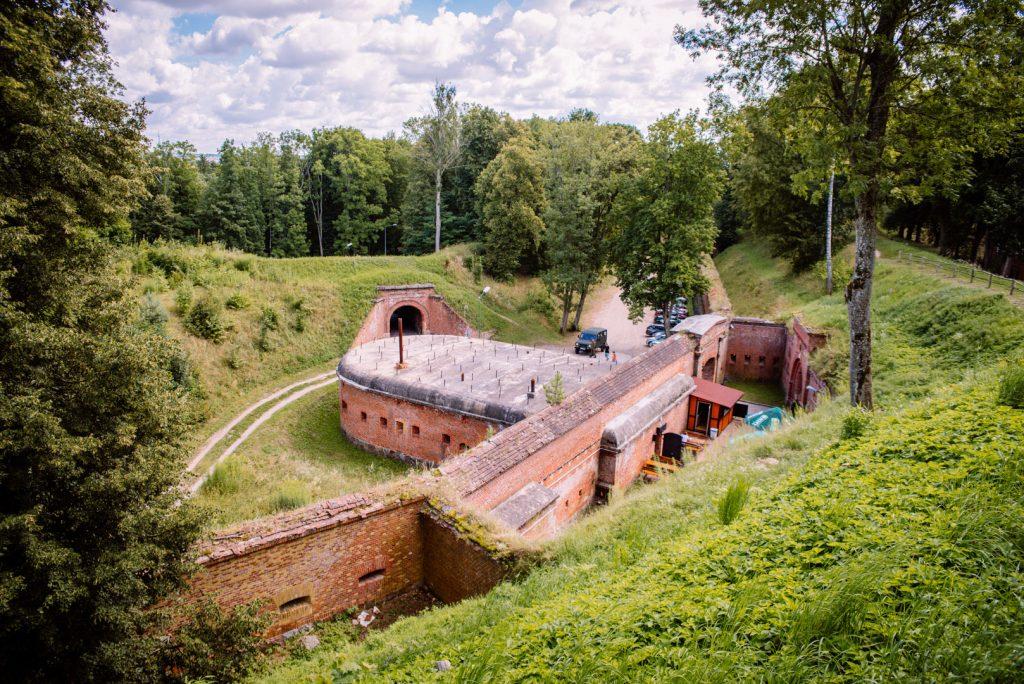 Mury Twierdzy Boyen w Giżycku, widok ze skarpy ukazujący forteczne budynki oraz wejścia do nich. Obiekt położony w małym wąwozie otoczony lasem.
