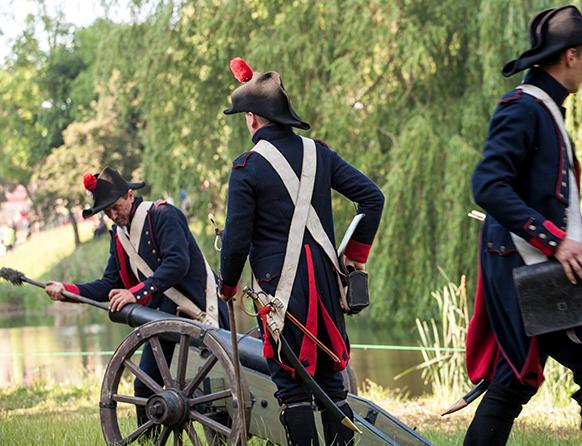 Inscenizacja Bitwy pod Heilsbergiem, na pierwszym planie trzech żołnierzy ubranych w stroje wojskowe z tamtej epoki a dwóch z nich w tym jeden czyści lufę przygotowując działo armatnie do wystrzału.