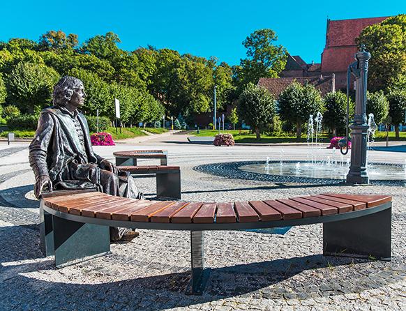 Zdjęcie przedstawia plac z małą fontanną wokół której stoją półokrągłe ławki z drewnianymi siedziskami oraz pomnikiem siedzącym na jednaj z ławek.