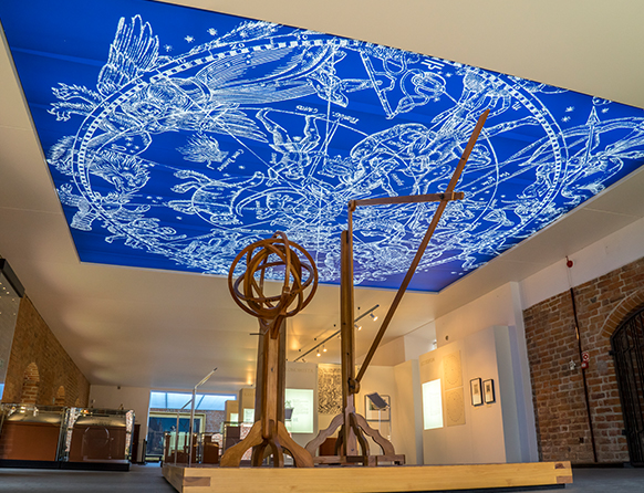 Zdjęcie przedstawia wnętrze sali z niebieskobiałym sufitem będącym częścią Muzeum Mikołaja Kopernika we Fromborku.