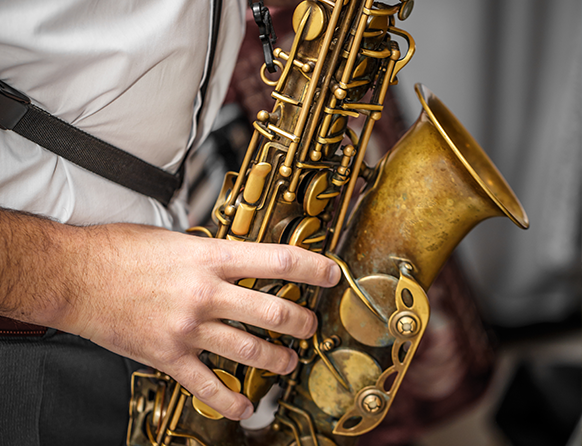Zdjęcie przedstawia zbliżenie złotego saksofonu podczas gry muzyka w Domu Konesera.