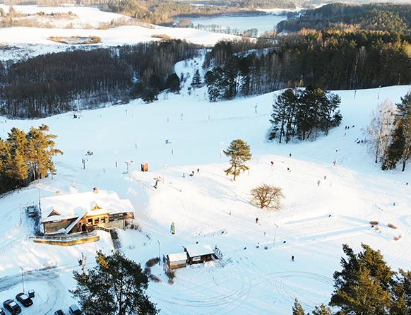 Zdjęcie wykonane z lotu ptaka, przedstawiające zimę na Górze Czterech Wiatrów niedaleko Mrągowa. Wszystko oprócz drzew pokryte jest białym śniegiem, a na górze szaleją miłośnicy zimowych sportów takich jak jazda na nartach.