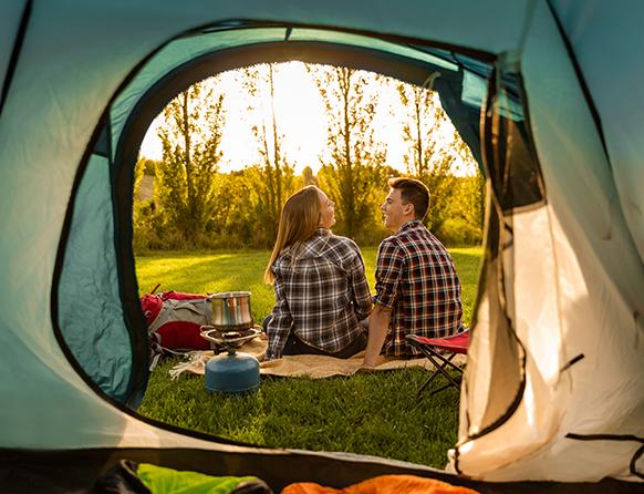 Para dziewczyna i chłopiec uśmiechniętych młodych osób,  podobnie ubranych, siedzących przed otwartym namiotem.