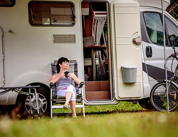 Kobieta odpoczywająca przy otwartych drzwiach mobilnego kampera, siedząc na turystycznym krześle popija kawę.